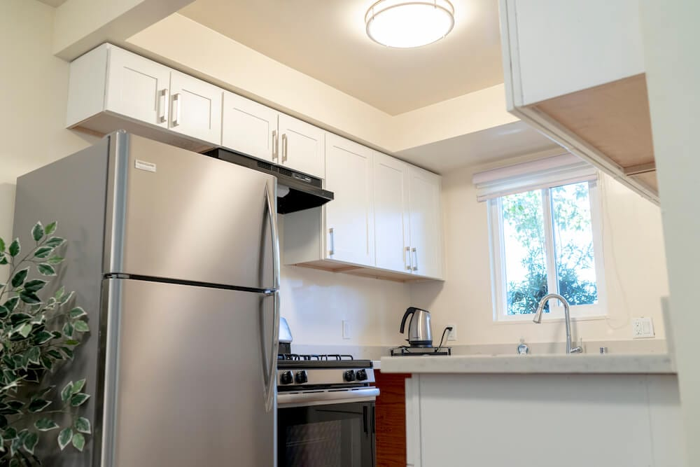 Kitchen with stainless steel refrigerator and stove from LA Intern student housing